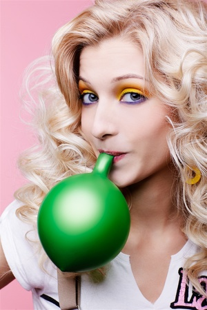 portrait of beautiful blonde party girl blowing up green balloon photo
