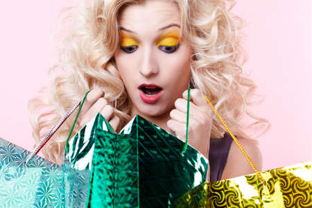expression portrait of customer blonde girl with shopping bags looking shocked photo