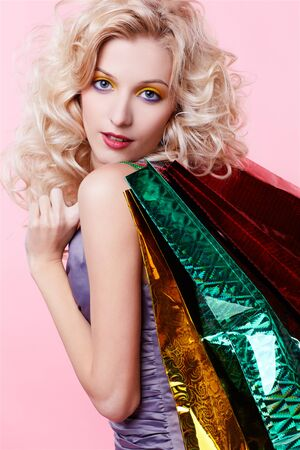 portrait of customer curly blonde girl carrying shopping bags photo