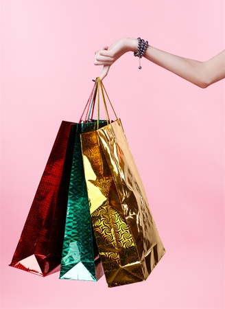 body part portrait of customer girls arm holding shopping bags on one manicured finger photo