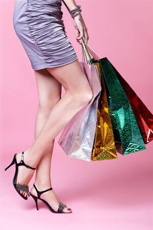 body part portrait of customer long legged girl in court shoes with shopping bags photo