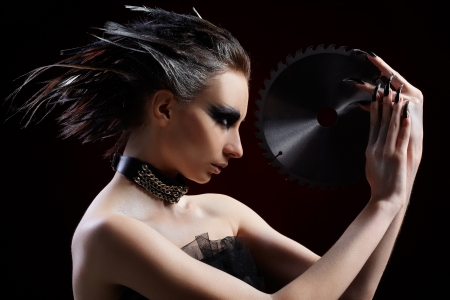 portrait of beautiful girl with bird of prey fantasy make-up with circular saw blade photo