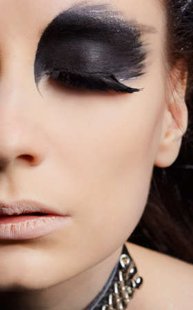 close-up portrait of beautiful girl with bird of prey fantasy make-up photo