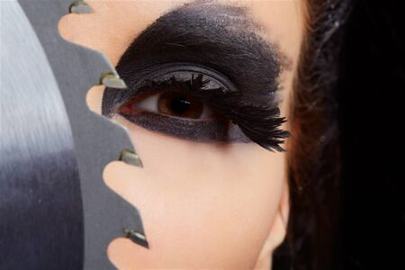 close-up portrait of beautiful girl with bird of prey fantasy make-up with circular saw blade photo