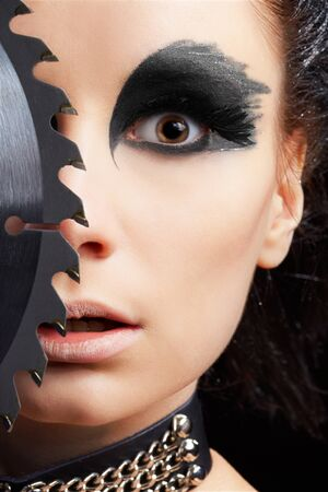 close-up portrait of beautiful girl with bird of prey fantasy make-up with circular saw blade looking surprised and shocked photo
