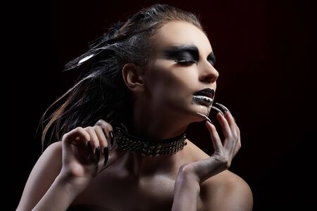 portrait of beautiful girl with bird of prey fantasy make-up pulling collar on her neck. silver paint flowing from lips photo