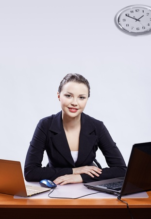 office portrait of beautiful friendly young business woman sitting at her workplace with two laptops on gray photo