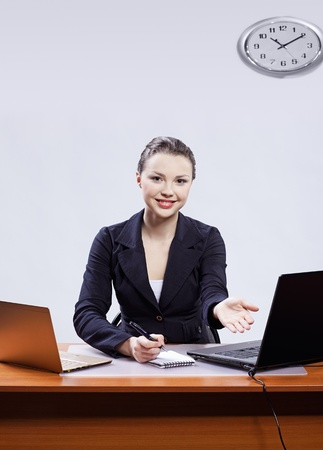 office portrait of beautiful friendly young business woman sitting at her workplace with two laptops and inviting to have a seat photo