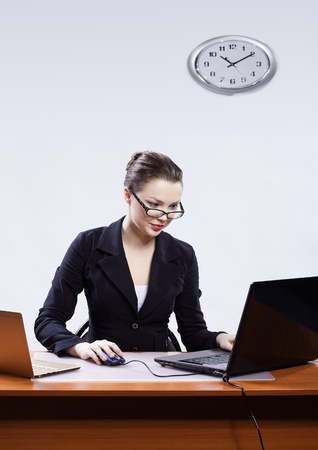 block note: office portrait of beautiful young business woman in glasses sitting at her workplace with two laptops and block note on gray