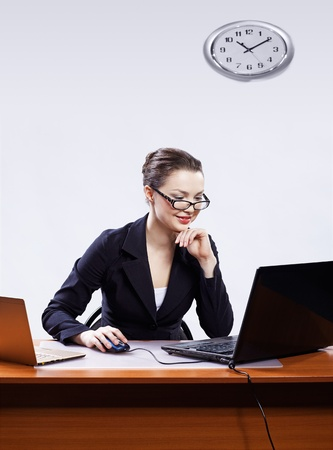 office portrait of beautiful happy young business woman in glasses sitting at her workplace with two laptops and on gray photo