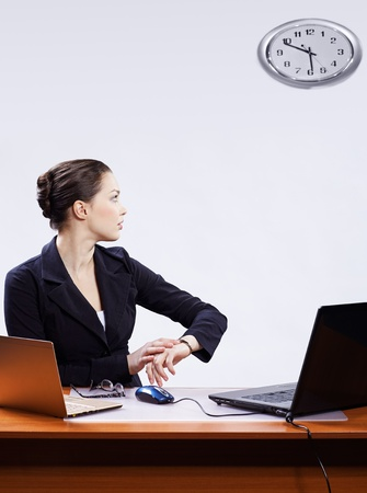 office portrait of beautiful young business woman sitting at her workplace with two laptops on gray and regulating her watches with clocks on wall photo