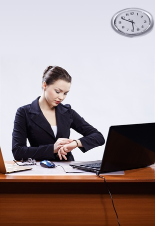 office portrait of beautiful young business woman sitting at her workplace with two laptops on gray and regulating her watches photo