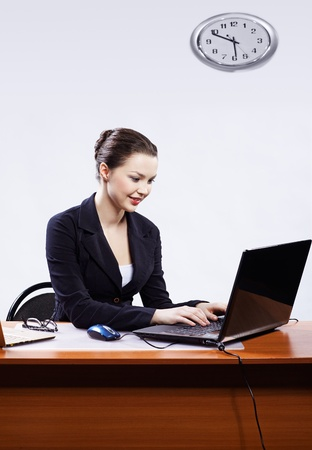 office portrait of beautiful young business woman sitting at her workplace with two laptops on gray photo