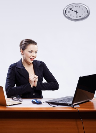 office portrait of beautiful young business woman sitting at her workplace with two laptops on gray and looking surprised and delighted photo