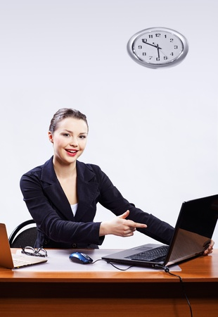 office portrait of beautiful friendly business woman sitting at her workplace and pointing on laptop photo