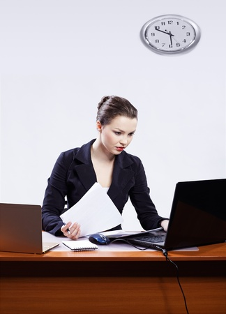 concetrated: office portrait of beautiful serious concetrated business woman at her workplace with documents and two laptops on gray