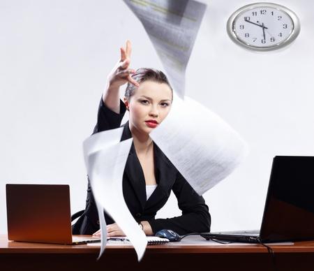 segretario: Ufficio ritratto di donna bella business insoddisfatto con due computer portatili con rabbia gettando documenti per la fotocamera