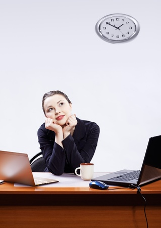 office portrait of beautiful young business woman at her workplace with two laptops having coffee break photo