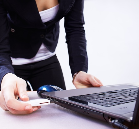 inserting: girls hand inserting usb flash memory into laptop header Stock Photo