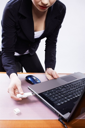 insert: girl inserting usb flash memory into laptop header Stock Photo