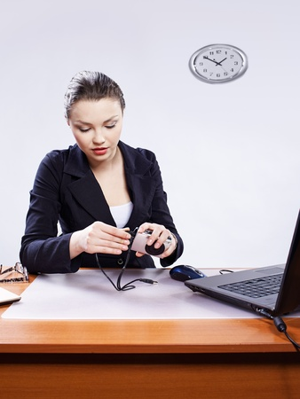 office portrait of beautiful young woman sitting with laptop and inserting usb wire into compact digital camera header photo
