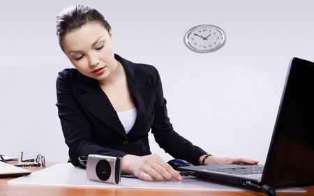 office portrait of beautiful young woman inserting usb wire of compact digital camera into laptop header photo