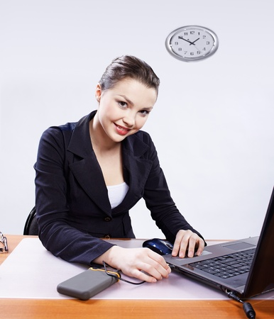 office portrait of beautiful young woman inserting usb wire of portable hard drive into laptop header Stock Photo - 8658224