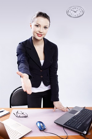 welcome desk: office portrait of beautiful happy business woman standing from her deck and stretching her hand for handshake at her workplace with two laptops on gray