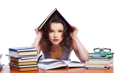 portrait of beautiful brunette student girl sitting among the books Stock Photo - 8658262