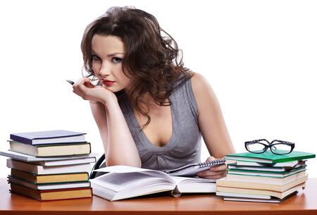 portrait of beautiful brunette student girl sitting among the books and writing in blocknote Stock Photo - 8658337