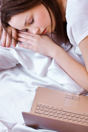 portrait of beautiful girl sleeping in bedroom on linen with notebook photo