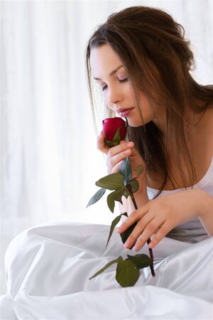 portrait of beautiful girl relaxing in bedroom on linen smelling red rose Stock Photo - 8806172
