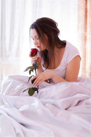 portrait of beautiful girl relaxing in bedroom on linen smelling red rose photo