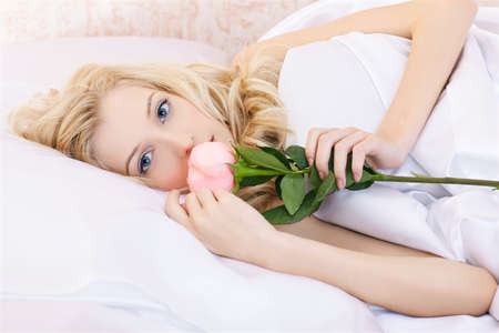 portrait of beautiful blonde girl relaxing in bedroom on linen with pink rose Stock Photo - 8806154