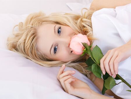 portrait of beautiful happy blonde girl relaxing in bedroom on linen with pink rose photo