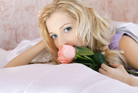 portrait of beautiful blonde girl relaxing in bedroom on linen with pink rose Stock Photo - 8806227