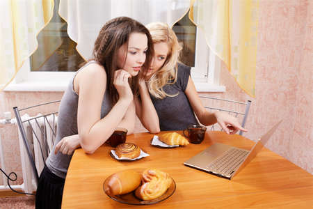portrait of two girls with laptop drinking tea wit buns and rolls photo