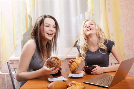 portrait of two happy girls with laptop drinking tea wit buns and rolls photo