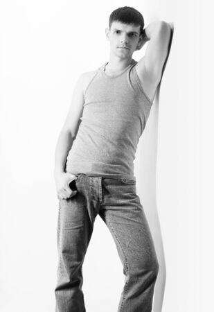 portrait of young handsome brunet guy in undershirt and jeans posing on gray Stock Photo - 8806278