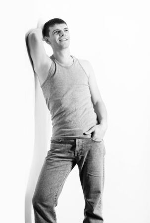 portrait of young handsome brunet guy in undershirt and jeans posing on gray Stock Photo - 8806275