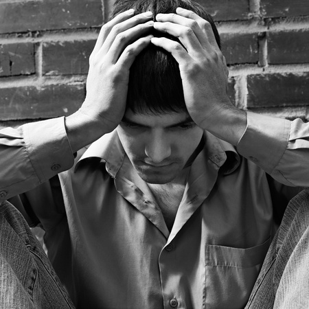 portrait of young brunet guy in depression sitting near red brick wall photo