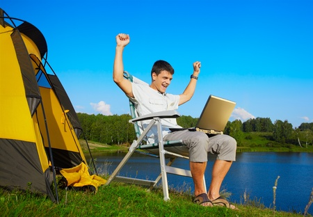 expression portrait of succesful man with laptop sitting in folding chair near camp tent outdoors photo