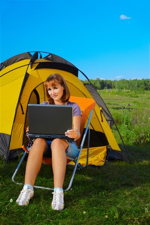 outdoor portrait of beautiful happy woman with laptop sitting in folding chair near camp tent Stock Photo - 8806327
