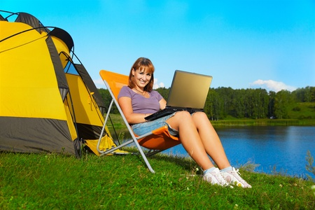 outdoor portrait of beautiful happy woman with laptop sitting in folding chair near camp tent photo