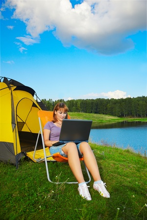 outdoor portrait of beautiful woman with laptop sitting in folding chair near camp tent photo