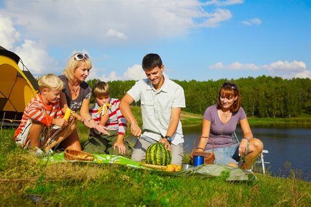 outdoor portrait of happy families at the picnic, young man is cutting watermelon Stock Photo - 8806330