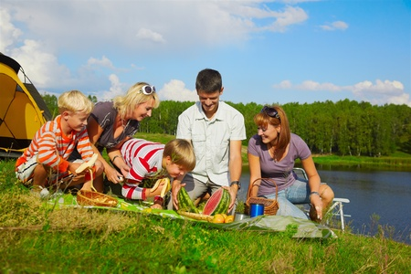 outdoor portrait of happy families at the picnic, going to eat watermelon cut in two halfs. Stock Photo - 8806326