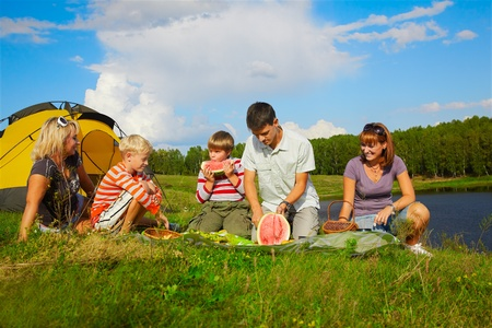 family picnic: outdoor portrait of happy families at the picnic, young man is cutting watermelon
