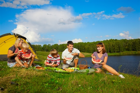 family picnic: outdoor portrait of happy families enjoying watermelon at the picnic near camp tent