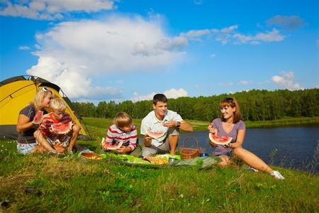 pique nique en famille: portrait en plein air de familles heureuses jouissant de past�que au pique-nique pr�s de camp tente Banque d'images
